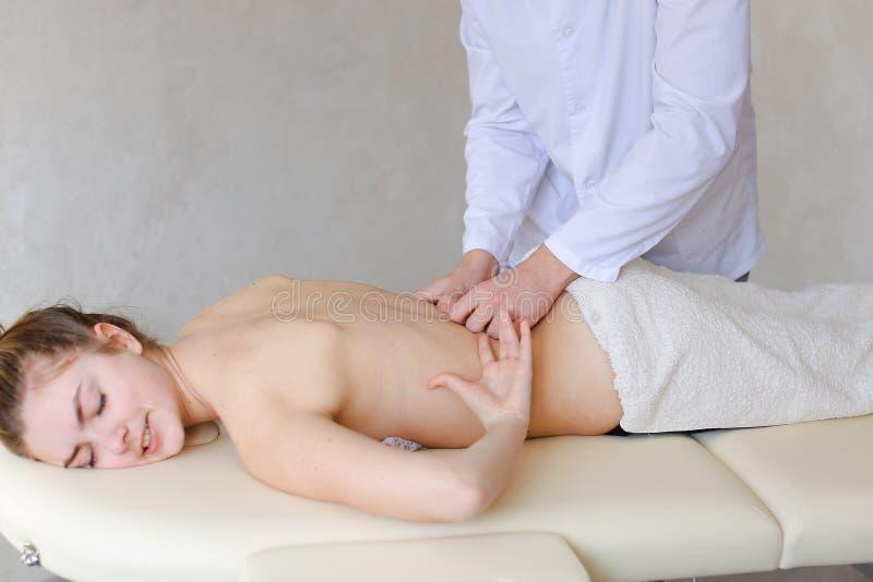 De sterke kerelmasseur maakt het herstellen van procedure voor rug van meisje aan royalty-vrije stock afbeeldingen