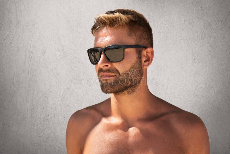 De sterke machomens met modieus kapsel, varkenshaar, stellen naakt tegen grijze concrete muur, die in sunglasess dragen, die conf royalty-vrije stock afbeelding