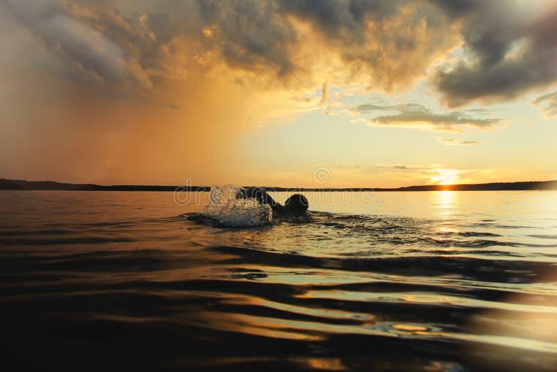 De sterke man zwemt in het meer bij zonsondergang na de regen royalty-vrije stock foto's