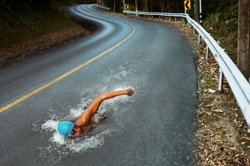 De sterke Mens zwemt op de Weg van het Asfalt royalty-vrije stock afbeelding