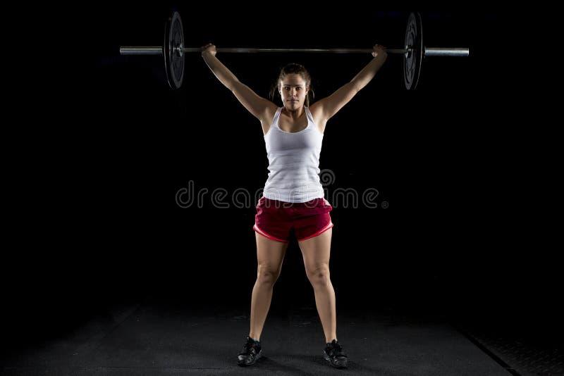 De sterke sexy vrouw rukt heel wat gewicht weg stock fotografie