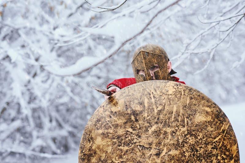 De sterke Spartaanse strijder wacht op aanval in de winterbos royalty-vrije stock afbeelding