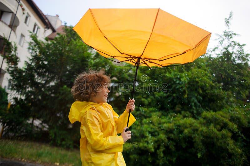 De sterke wind heeft een paraplu in de handen van de jongen ontrukken stock afbeeldingen