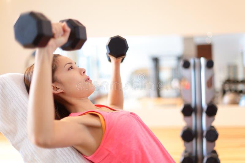 De sterkte van de gymnastiekvrouw opleiding het opheffen gewichten stock afbeeldingen