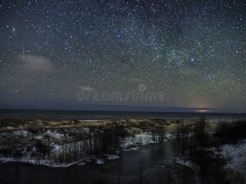 De sterren en de sneeuw van de nachthemel op overzeese kust stock foto