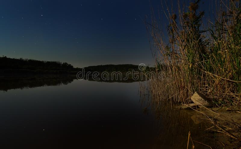 De sterren in de nachthemel worden weerspiegeld in de spiegel vlotte oppervlakte van het meer, en de maan stock foto's
