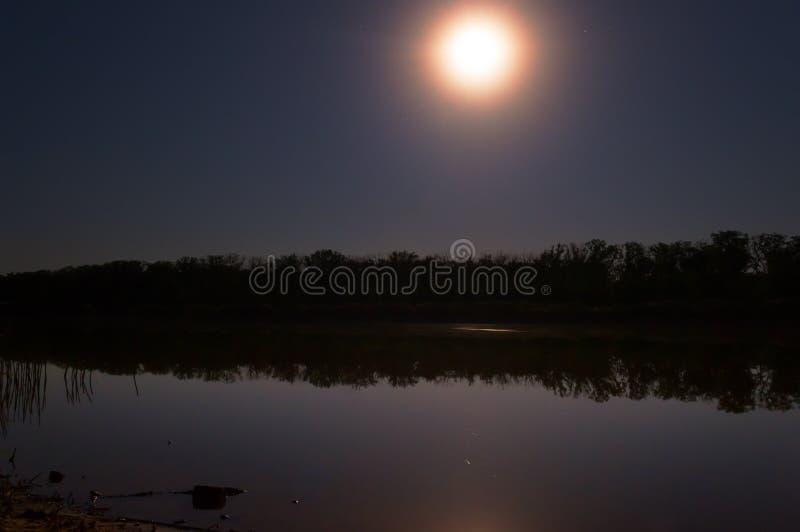 de sterren in de nachthemel worden weerspiegeld in de spiegel vlotte oppervlakte van het meer, en de maan verlicht royalty-vrije stock foto
