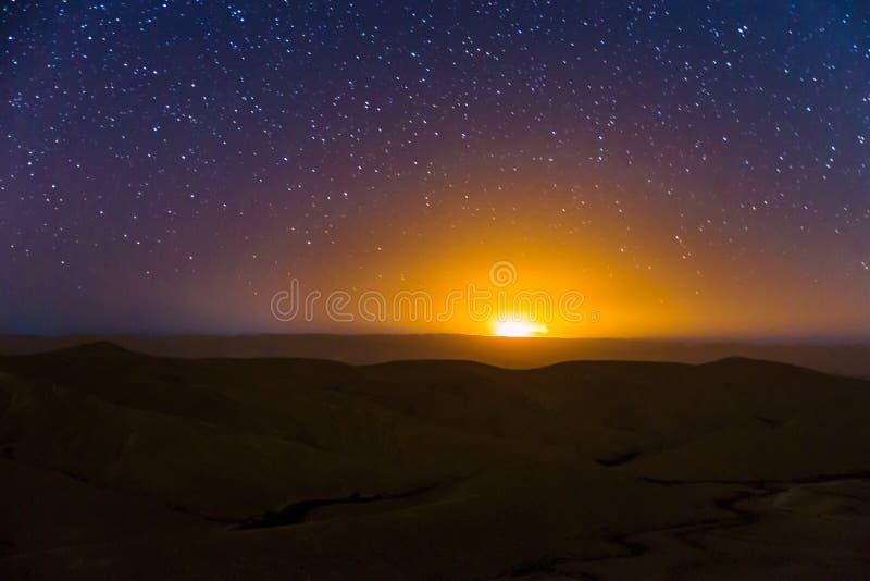 De sterren van de nachthemel over de zonsonderganglicht van woestijnheuvels stock foto
