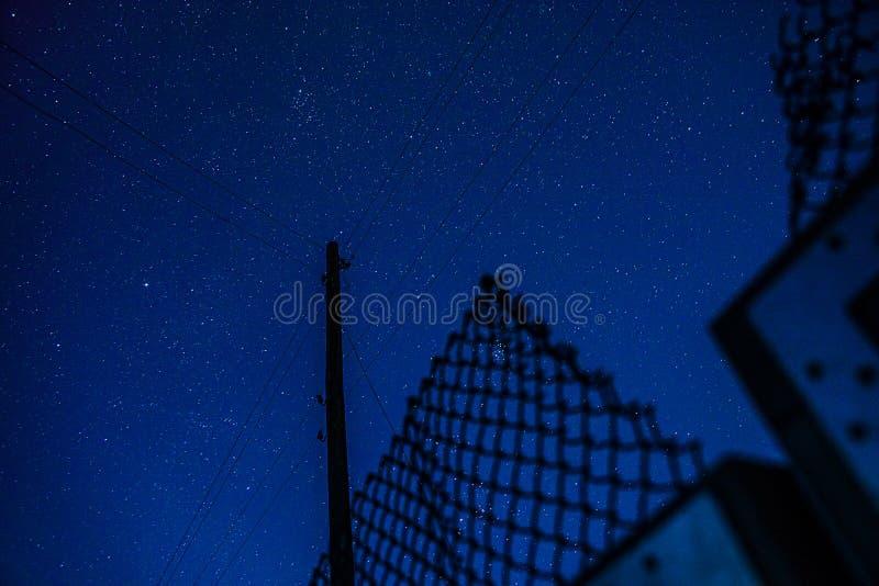 De sterrige hemel met een silhouet van een pool met draden en een net schermen royalty-vrije stock afbeeldingen
