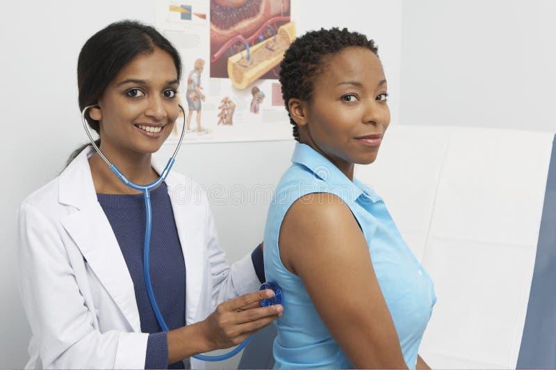 De Stethoscoop van artsenexamining patient using royalty-vrije stock foto