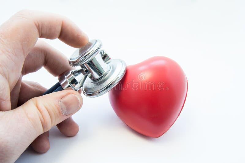 De stethoscoop van de artsenholding in zijn hand, onderzoekt hartvorm voor aanwezigheid van ziekten van cardiovasculair systeem F stock foto's
