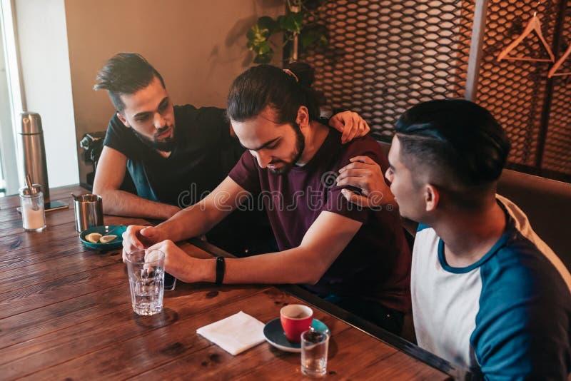 De steunende jonge mensen moedigen hun ontroostbare vriend aan De Arabische kerels juichen hem omhoog in restaurant toe Het conce stock afbeelding
