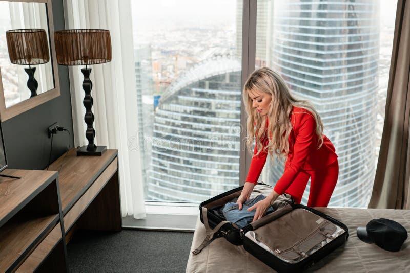 De stewardess in rode eenvormig komt in een hotelruimte aan met zwarte koffer Rust in de doorgangsstad vóór de retourvlucht stock fotografie