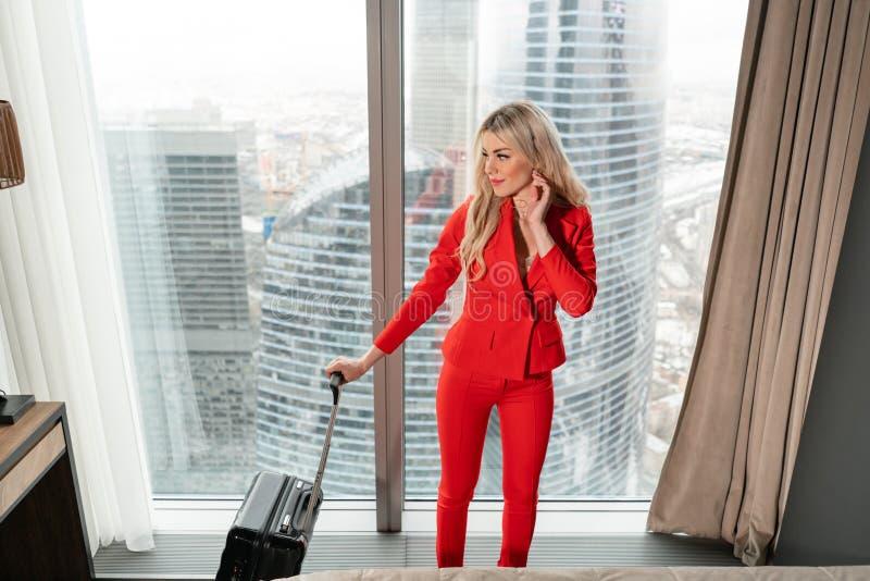 De stewardess in rode eenvormig komt in een hotelruimte aan met zwarte koffer Rust in de doorgangsstad vóór de retourvlucht stock afbeelding