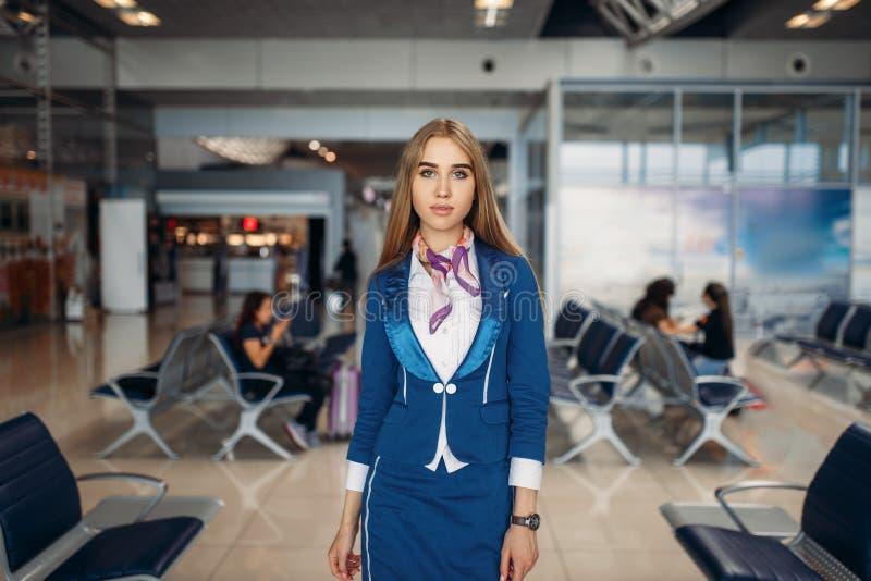 De stewardess stelt in luchthaven wachtend gebied stock foto's