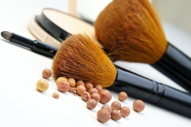 De stichting, het poeder, bronzer en de borstels van de make-up stock foto