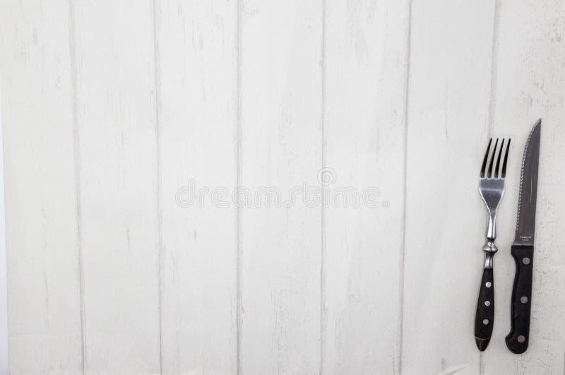 De stijl houten lijst van de Provence, achtergrond voor menu, bistro, koffie, restaurant Mes, vork die op een lichte houten achte royalty-vrije stock fotografie