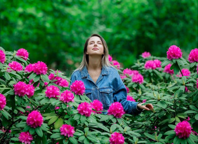 De stijlvrouw dichtbij rododendronbloemen in a grarden royalty-vrije stock afbeelding