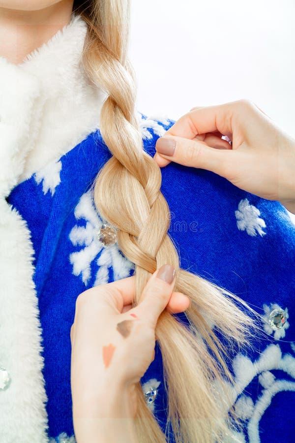 De stilist ` s overhandigt vlechtenvlecht voor Sneeuwmeisje stock foto