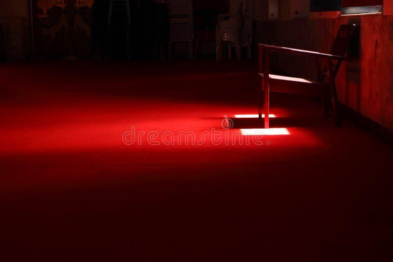 De stoel in dark op het rode tapijt royalty-vrije stock foto's