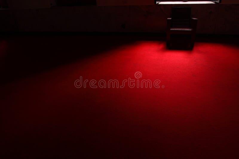 De stoel in dark op het rode tapijt stock afbeeldingen