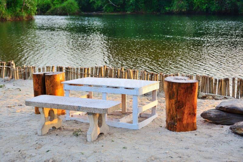De stoel en witte tafel op het zand met water als achtergrond stock afbeeldingen
