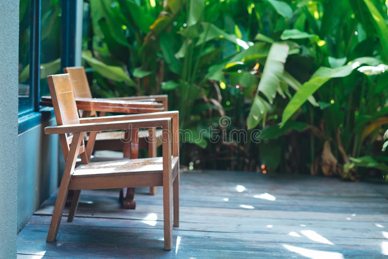 de stoel plaatste houten vloer buiten de ruimte in ochtend Groene pla stock fotografie