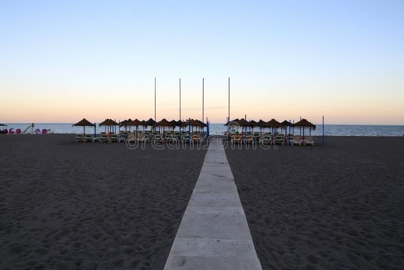 De stoel van de strandzitkamer en strandparaplu bij eenzaam zandig strand Costa del Sol (Kust van de Zon), Malaga in Andalusia, S stock foto