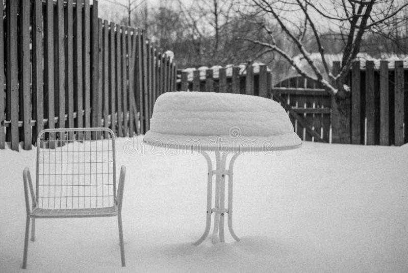 De stoel van het binnenplaatsterras en sneeuw behandelde lijst in zwart-wit royalty-vrije stock foto