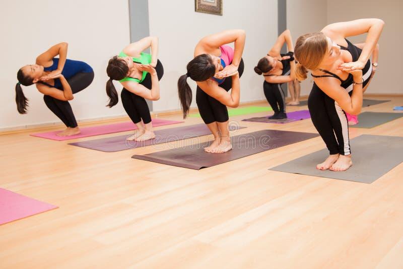 De stoeldraai stelt in een yogaklasse stock afbeeldingen