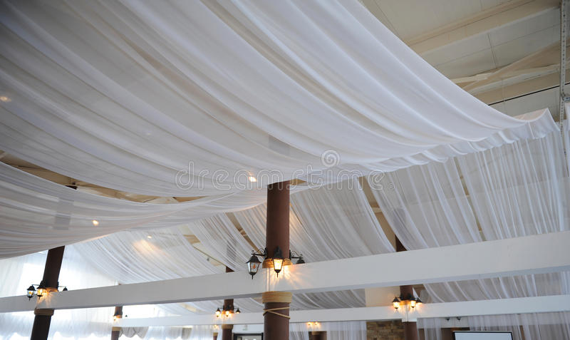 De stof drapeert op het restaurantplafond Heldere binnenlandse, aangestoken lantaarn Het decor voor de huwelijkspartij stock afbeeldingen