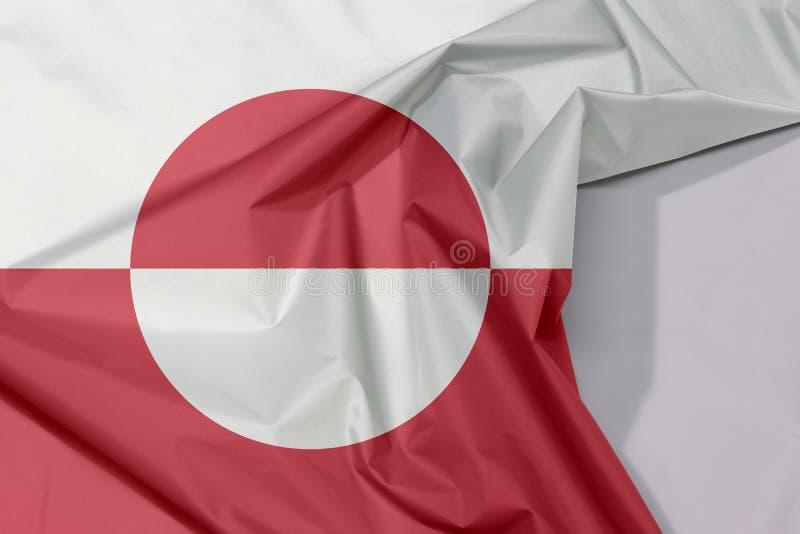 De stoffenvlag van de stoffenvlag van Groenland omfloerst en vouwt met witte ruimte royalty-vrije stock afbeelding