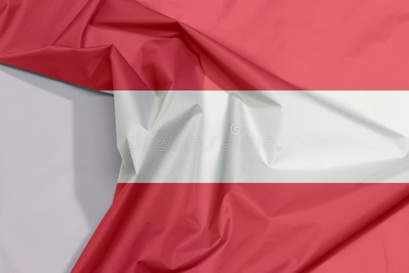 De de stoffenvlag van Oostenrijk omfloerst en vouwt met witte ruimte royalty-vrije stock foto's