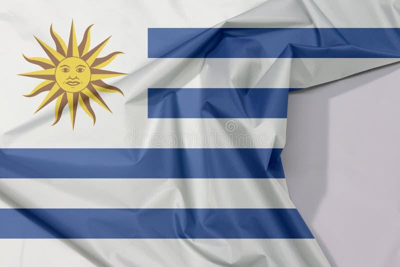 De de stoffenvlag van Uruguay omfloerst en vouwt met witte ruimte royalty-vrije stock afbeelding