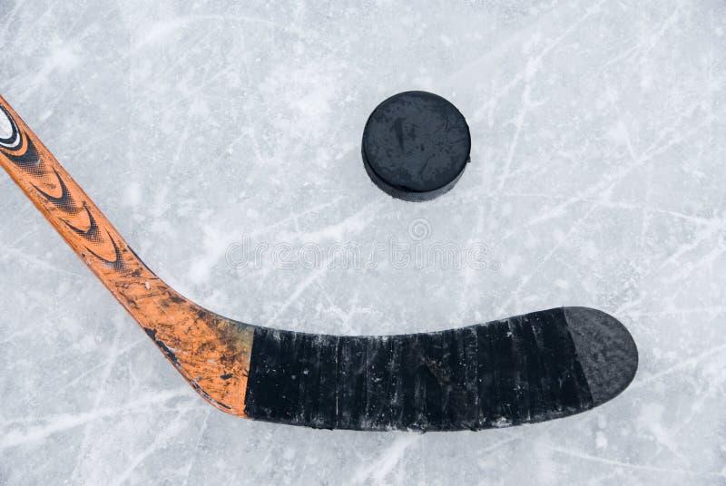 De stok en de puck van het ijshockey op ijs stock fotografie