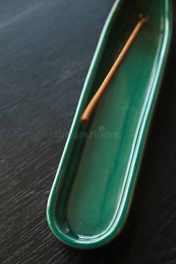De stok van de kuuroordwierook op de groene ceramische houder van de jadekleur stock foto's