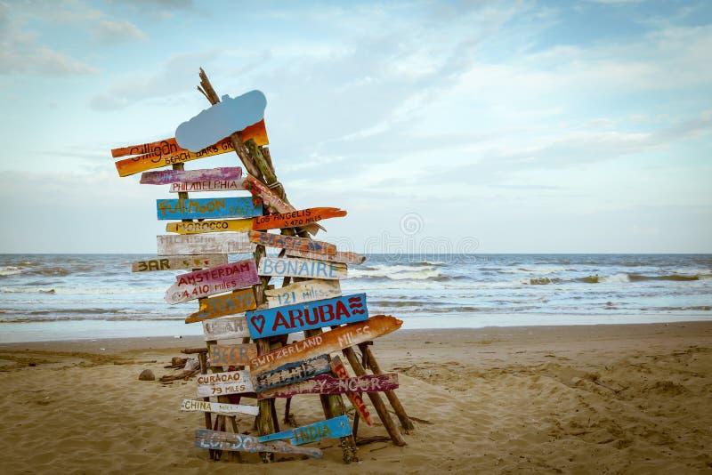 De stok van reisverkeersteken op hout of vuurtent bij zand beac stock fotografie