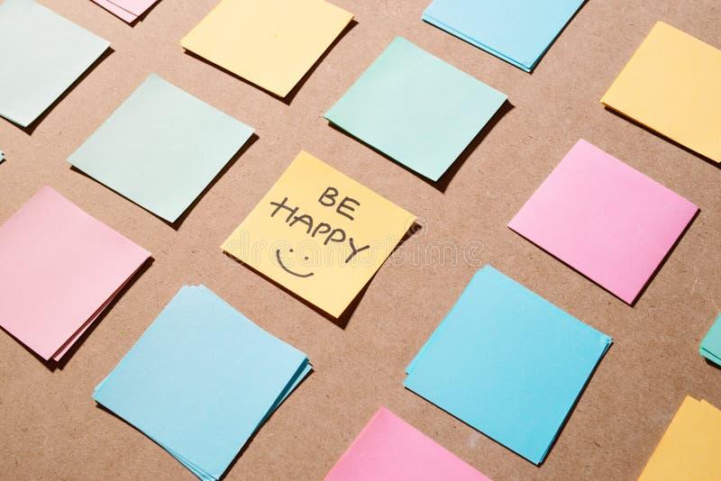 De stokken nemen nota van document met tekst - gelukkig ben op houten achtergrond voor r stock foto's