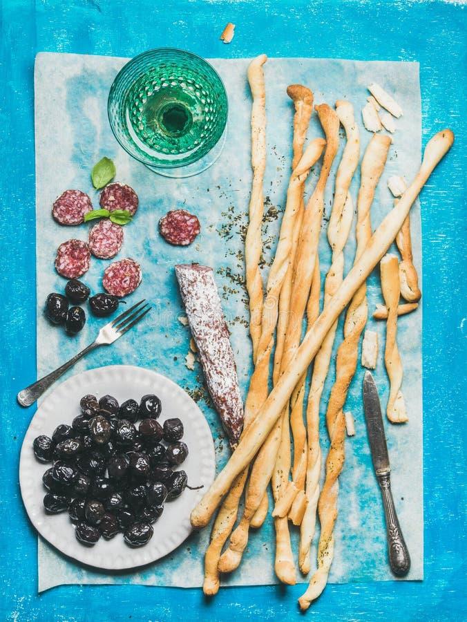 De stokken van het Grissinibrood, worst, olijven en witte wijn, blauwe achtergrond stock afbeeldingen