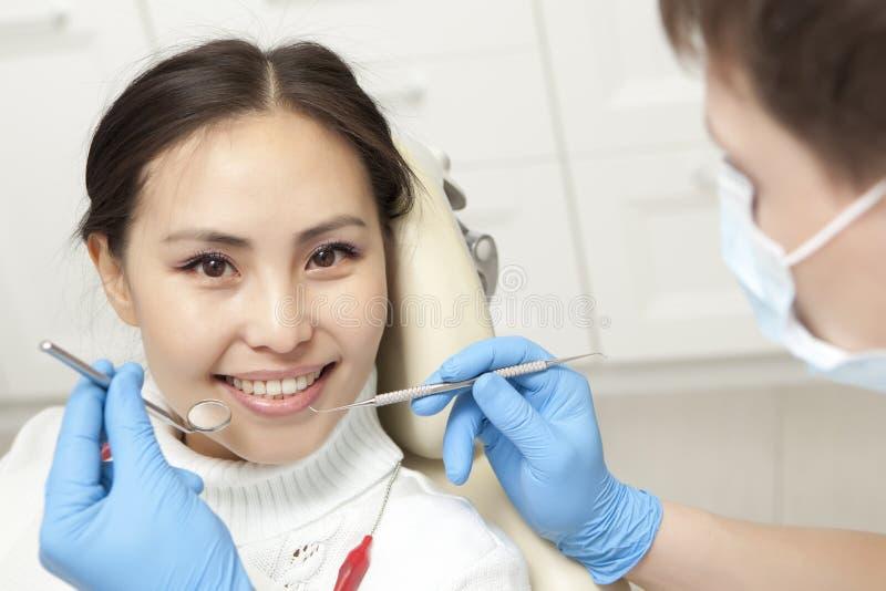De stomatologieconcept - mannelijke tandarts die met spiegel patiënt controleren stock foto's