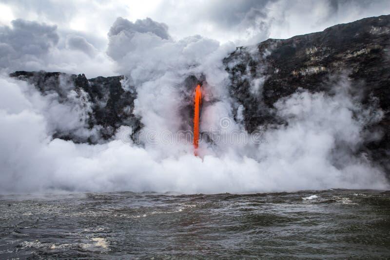 De stoom barst van koude oceaan los aangezien de hete lava in water giet stock foto's