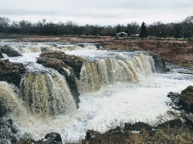 De stora Sioux River flödena över vaggar i Sioux Falls South Dakota med sikter av djurliv, fördärvar, parkerar banor, drevspårbro royaltyfria foton
