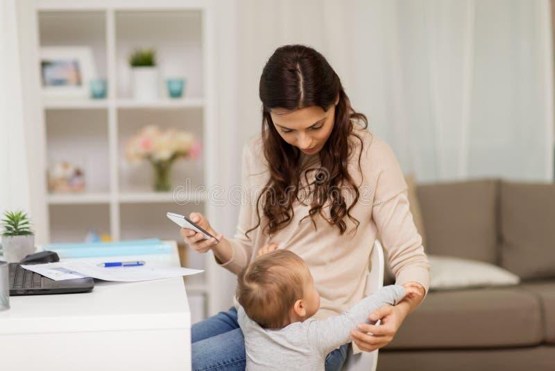 De storende moeder die van de babyjongen thuis werken stock afbeeldingen