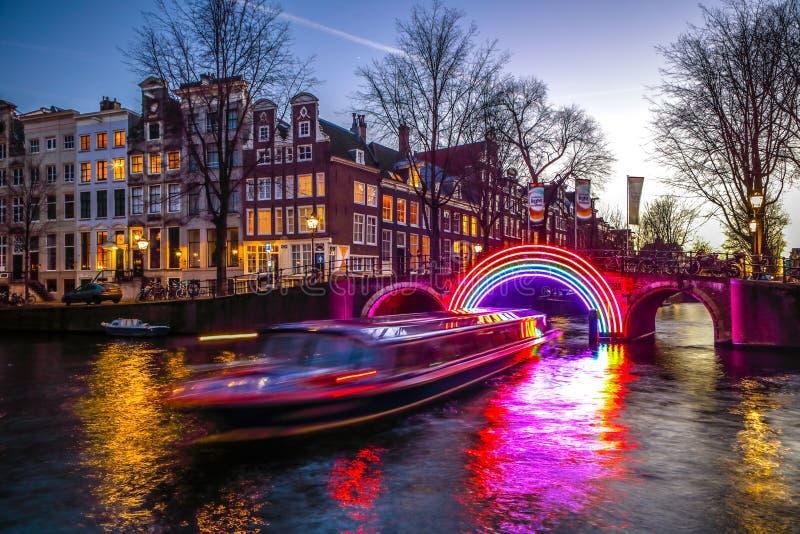 De stormloop van cruiseboten in nachtkanalen Lichte installaties op nachtkanalen van Amsterdam binnen Licht Festival stock afbeeldingen