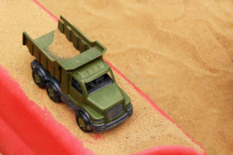 De stortplaatsvrachtwagen maakt grond op het zand bij een bouwwerf leeg royalty-vrije stock afbeelding