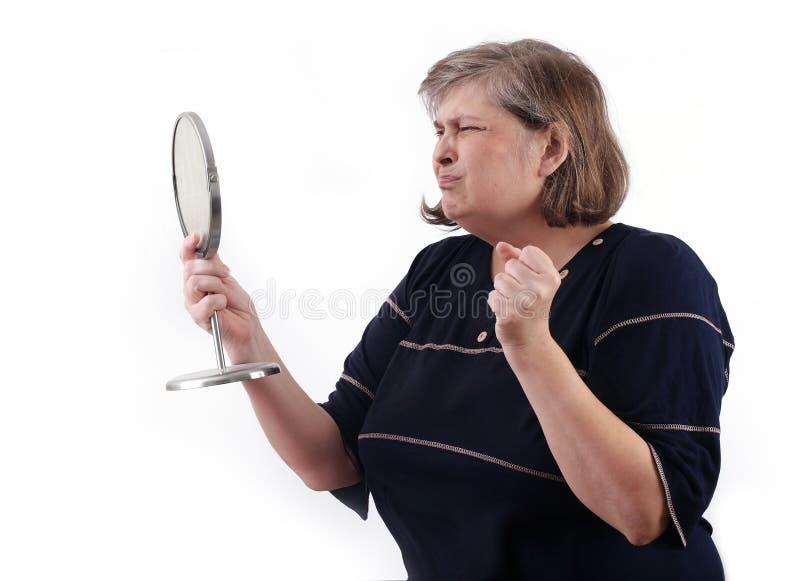 De stout womancried, kijkend in een spiegel royalty-vrije stock afbeelding
