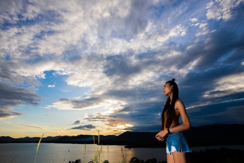 De straal van de zonsondergangwolk aan jonge volwassen Aziatische woma stock afbeeldingen