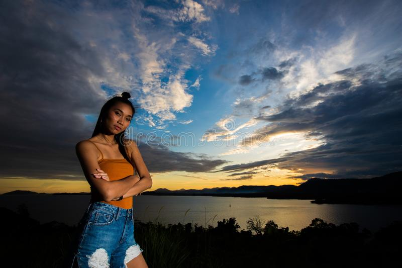De straal van de zonsondergangwolk aan jonge volwassen Aziatische woma stock fotografie