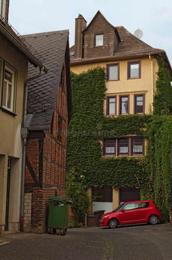 De straat met een binnenplaats van een grote woningbouw Kleine rode die auto in de hoek van binnenplaats wordt geparkeerd Histori stock foto