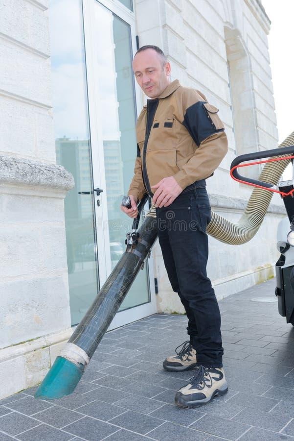 De straat schonere werken met stofzuiger op straat stock foto